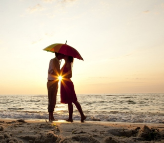 Couple Kissing Under Umbrella At Sunset On Beach - Obrázkek zdarma pro iPad