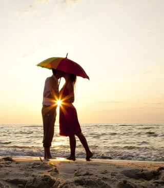 Couple Kissing Under Umbrella At Sunset On Beach - Obrázkek zdarma pro 176x220