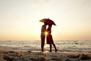 Couple Kissing Under Umbrella At Sunset On Beach - Obrázkek zdarma