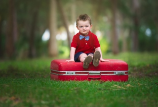 Cute Boy Sitting On Red Luggage - Obrázkek zdarma pro HTC Desire HD